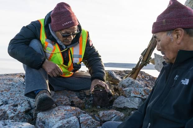 Roger Hitkolok, right, and Jimmy Evalik inspect a tin can at a cairn on Sutton Island, Nunavut. The can contained a note from a captain who had moored at the island to weather a storm.