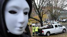 A masked protester watches city crews in yellow jackets clear out tents and debris after police moved in to remove members of the Occupy Toronto movement from a park. (J.P. MOCZULSKI For The Globe and Mail)