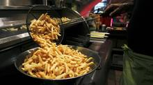 A cook prepares fries (© Thierry Roge / Reuters)