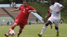 Canada's Nikolas Ledgerwood, left, controls the ball under pressure from Cuba's Francisco Serrano during a 2014 World Cup qualifying game at the Pedro Marrero stadium in Havana, Cuba, Friday, June 8, 2012. (Franklin Reyes/AP)