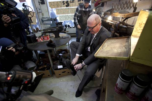 Finance Minister Michael de Jong tries on his newly-soled shoes at Olde Towne Shoe Repair in Victoria as owner Mike Waterman looks on. The photo-op has become a yearly ritual ahead of the provincial budget.