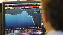 A trader watches a graph showing the fall of the Euro in Paris on Friday. (Remy de la Mauviniere/AP)