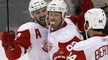 Detroit Red Wings Johan Franzen (C) celebrates his fourth goal against the Ottawa Senators with teammates Henrik Zetterberg (L) and Todd Bertuzzi during the third period of their NHL hockey game in Ottawa February 2, 2011 REUTERS/Chris Wattie (CHRIS WATTIE)