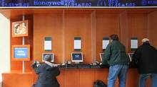 Customers at a TD Ameritrade office check online stock prices Friday, April 13, 2007 in New York. (MARK LENNIHAN/AP)