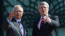 Canada's Prime Minister Stephen Harper gestures next to Malaysia's Prime Minister Najib Razak during a photo call outside Najib's office in Putrajaya, near Kuala Lumpur October 6, 2013. (Samsul Said/REUTERS)