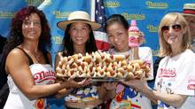 Women's contestants Larell Marie Mele, Juliet Lee, Sonya Thomas and Laura Leu pose together after their official weigh-in for Nathan's Famous Fourth of July International Hot Dog Eating Contest during a ceremony at City Hall Park, July 1, 2011 in New York. (Associated Press)