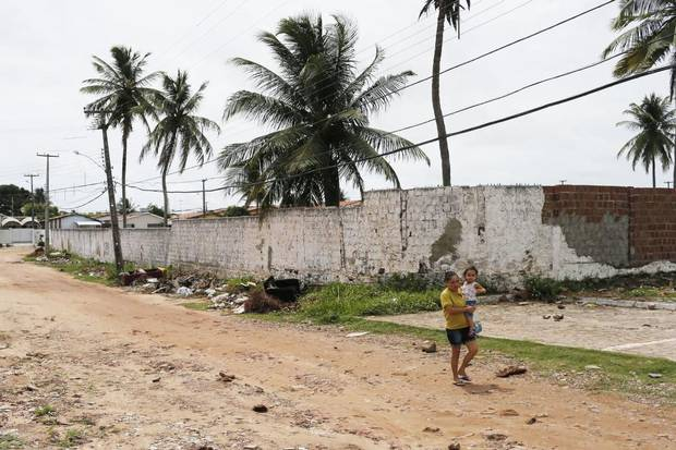 A woman walks with a child in her arms on a sandy road in Joao Pessoa. About 1.5 million people are believed to have been infected by the Zika virus in Brazil since 2014.