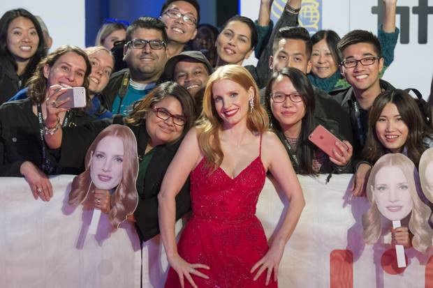Jessica Chastain poses with fans as she arrives for the premiere of Woman Walks Ahead.