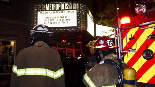 Police and firefighters work at the rear of a nightclub where a gunman shot and killed at least one person during the Parti Québécois victory rally on Sept. 5, 2012 in Montreal. (Paul Chiasson/THE CANADIAN PRESS)