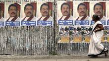 A woman walks past posters bearing the portrait of Sri Lankan President Mahinda Rajapaksa along a main street in central Colombo recently. (DAVID GRAY/REUTERS/David Gray)