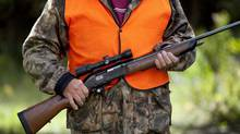 A rifle owner walks around his hunting camp west of Ottawa on Sept. 15, 2010. (Sean Kilpatrick/The Canadian Press/Sean Kilpatrick/The Canadian Press)