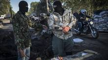 Left: Pro-Russian activists guard their own checkpoint outside Sloviansk, a militant stronghold. , and the Interior Ministry said fighting around checkpoints had turned deadly.