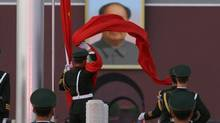 A paramilitary police officer collects the Chinese national flag during a flag-lowering ceremony in front of a giant portrait of the late chairman Mao Zedong on Beijing's Tiananmen Square, Nov. 12, 2012. (JASON LEE/REUTERS)