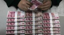 An employee counts yuan banknotes at a branch of Bank of China in Taiyuan, Shanxi province. European and U.S. officials have been pressing China for years to do more to open up the yuan to market forces. (STRINGER SHANGHAI/REUTERS)