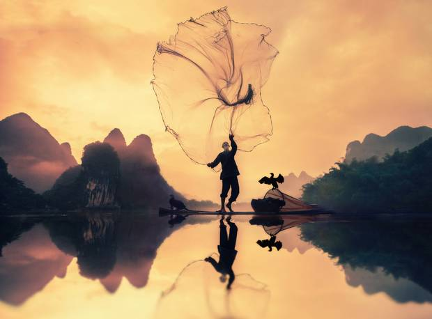 Saudi Arabian photographer, Khalid Alsabt, is recognized in the Travel category for his early morning photo of a Chinese fisherman throwing his net.