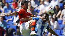 Espanyol's Kalu Uche, right, fights for the ball with Valencia's Ricardo Costa during their Spanish first division soccer league match at Cornella-El Prat stadium, near Barcelona on Sunday. (ALBERT GEA)