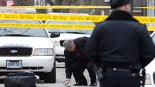 A member of the Police Special Investigations Unit inspects a used shell casing after Michael Eligon was fatally shot by the Police after allegedly threatening officers with scissors in Toronto on Friday February 3, 2012. (Chris Young For The Globe and Mail)