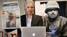 Julian Assange of the WikiLeaks website holds up a copy of The Guardian newspaper as he speaks to reporters in front of a Don McCullin Vietnam war photograph at The Front Line Club on July 26, 2010 in London, England. The WikiLeaks website has published 90,000 secret US Military records. The Guardian and The New York Times newspapers and the German Magazine Der Spiegel have also published details today. (Peter Macdiarmid/Peter MacDiarmid/Getty Images)