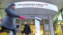 Pedestrians walk past The Canadian Press head office entrance in Toronto. (Graeme Roy/The Canadian Press)