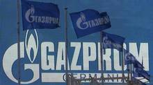 Flags fly near an advertising screen displaying the logo of Gazprom company, in St. Petersburg, November 14, 2013. (© Alexander Demianchuk / Reuter)