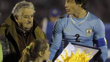 Uruguay's President Jose Mujica is seen in this photo giving Uruguay's captain Diego Lugano the national flag before an international friendly soccer match against Slovenia. (Matilde Campodonico/AP)