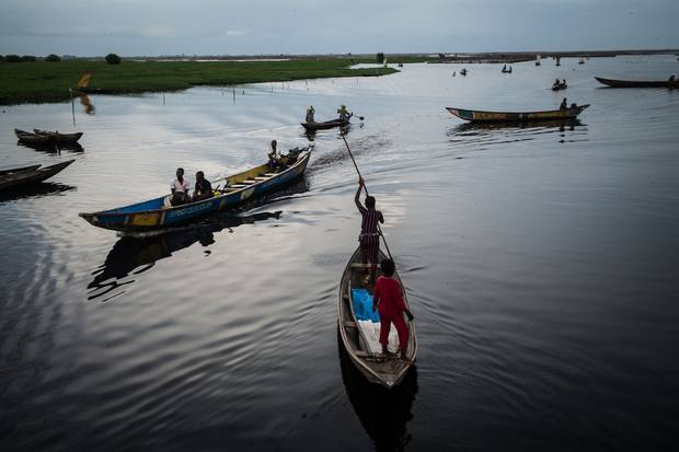 Sellers, passengers and fishermen navigate on the Ouémé River after leaving Ganvie wharf at the end of the day.