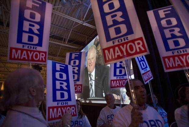 Rob Ford supporters hold signs as Ford is seen on a video screen during his 2014 campaign kick off.