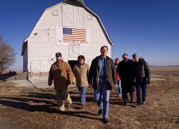 Al Gore walks out of a barn with members of the Roarson and Wilts families as he tours their farm in Sloan City, Iowa, on Jan. 13, 2000.
