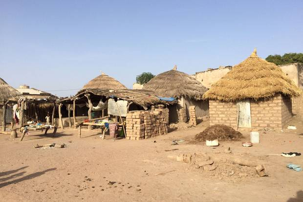 Back in Tambacounda province, most families live in mud brick houses like the ones shown at left. But families with relatives in Europe can afford modern cement houses.