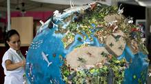 A woman looks at a model of the Earth during United Nations climate talks in Cancun, Mexico, on Nov. 30, 2010. (RONALDO SCHEMIDT/AFP/Getty Images)
