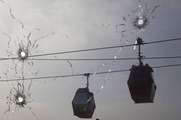 Cable cars move along, seen through a window pierced by bullet holes, on July 24, 2012, at a police station used by the UPP in Rio's Complexo do Alemao slum.