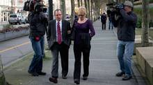 Karen Briker, centre right, walks with an unidentified man as she arrives at B.C. Supreme Court to testify at the Queen of the North passenger ferry sinking trial in Vancouver, B.C., on Monday March 4, 2013. Briker was on the bridge with her former lover fourth officer Karl Lilgert, who is on trial for criminal negligence, when the vessel ran aground and sank in 2006. (DARRYL DYCK/THE CANADIAN PRESS)