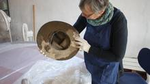 Textile conservator Gail Niinimaa holds a 1950s-era Boy Scouts stetson, part of the Museum of the Highwood's collection damaged during last year's floods in southern Alberta. (PATRICK WHITE/THE GLOBE AND MAIL)