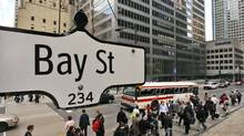 The Bay Street sign is pictured in the heart of the financial district as people walk by in Toronto. (Mark Blinch/Reuters/Mark Blinch/Reuters)