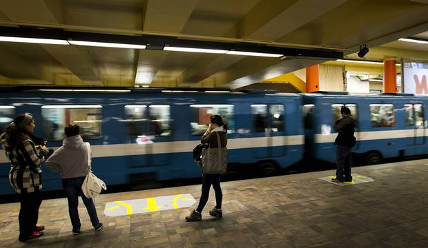 Passengers stand while a Montreal Metro train passes through a station in Montreal.
