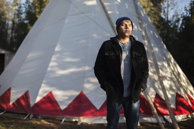 Rhode Thomas, a First Nations student at Trent University in Peterborough who is taking business specialized in Indigenous studies, stands by a tepee on campus in November.