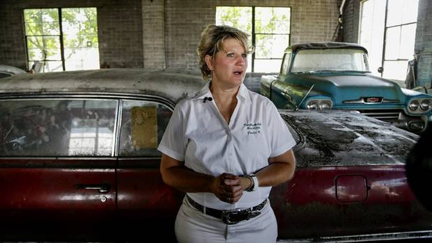 Auctioneer Yvette VanDerBrink stands in front of a 1963 Chevrolet Impala and a 1958 Cameo pickup truck, right, at the former Lambrecht Chevrolet car dealership in Pierce, Nebraska. (Nati Harnik/AP Photo)