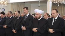 Syria's President Bashar al-Assad, centre,  performs prayers for Eid al-Adha, at al-Afram Mosque in Damascus Oct. 26, 2012, in this photograph released by Syria's national news agency SANA. (Sana/REUTERS)