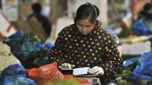 A vendor calculates her expenses at her vegetable store in a market in Hefei in central China's Anhui province Thursday, Jan. 9, 2014. China's inflation rate eased in December to 2.5 per cent amid signs the economy might be cooling. (AP Photo)