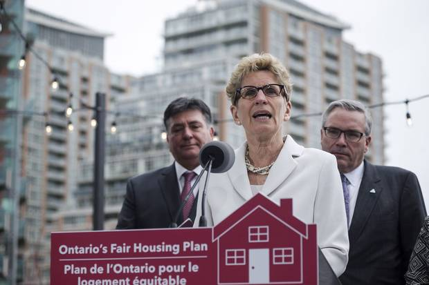 Ontario Premier Kathleen Wynne, middle, is joined by Ontario Finance Minister Charles Sousa, left, and Ontario Housing Minister Chris Ballard in Toronto to speak about Ontario's Fair Housing Plan on April 20, 2017.