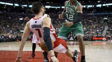 Toronto Raptors forward Andrea Bargnani (left) tumbles to the floor after battling for the ball with Boston Celtics guard Leandro Barbosa (right) during first half NBA action in Toronto on Wednesday February 6, 2013. (Frank Gunn/THE CANADIAN PRESS)