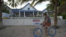 "A man rides a bicycle past the beachside entrance to the home of software company founder John McAfee in Ambergris Caye, Belize, Thursday Nov. 15, 2012. Software company founder John McAfee, who has been identified as a ""person of interest"" in the killing of his neighbor, 52-year-old Gregory Viant Faull, said Wednesday he is in hiding, unarmed and accompanied only by a young woman, changing locations and telephones frequently to stay one step ahead of a Belize police unit he says wants to kill him. (Jose Osorio/AP)"