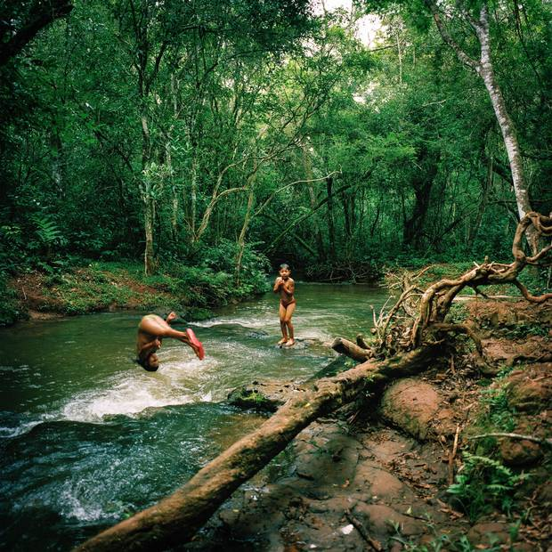 Tamil Flores, 9, left, and her brother Hudson Flores, 6, play in a stream in Guaiviry.