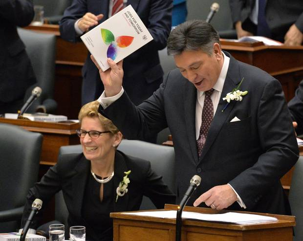 Ontario Finance Minister Charles Sousa, right, delivers the Ontario 2016 budget next to Premier Kathleen Wynne, left, at Queen's Park in Toronto on Feb. 25, 2016.
