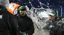 Saskatchewan Roughriders' coach Corey Chamblin has a bucket of water poured over him as the team celebrates winning the CFL West Final in Calgary, Alta., Sunday, Nov. 17, 2013. The Saskatchewan Roughriders beat the Calgary Stampeders 35-13. (JEFF MCINTOSH/THE CANADIAN PRESS)