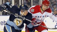 Pittsburgh Penguins center Sidney Crosby (L) and Mike Green (R) of the Washington Capitals fight for the puck during the first period of the NHL's Winter Classic hockey game at Heinz Field in Pittsburgh, Pennsylvania January 1, 2011. REUTERS/Jason Cohn (JASON COHN)