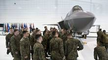Naval flight students inspect a U.S. Marine F-35 Joint Strike Fighter jet during a roll-out ceremony at Eglin Air Force Base in Florida on Feb. 24, 2012. (STRINGER/REUTERS)