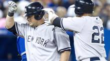 New York Yankees' Casey McGehee (left) celebrates with Andruw Jones after hitting a three run homer off Toronto Blue Jays pitcher Aaron Laffey during fourth inning MLB action in Toronto on Saturday, August 11 , 2012. THE CANADIAN PRESS/Chris Young (Chris Young/THE CANADIAN PRESS)