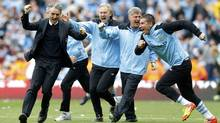 Manchester City manager Roberto Mancini (L) runs onto the pitch after winning their English Premier League soccer match against Queens Park Rangers at the Etihad Stadium in Manchester, northern England, May 13, 2012. (Phil Noble/Reuters/Phil Noble/Reuters)