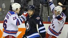 New York Rangers' Ryan Callahan (R) celebrates his game-winning goal with Ruslan Fedotenko (L) as Winnipeg Jets' Zach Bogosian skates to the bench during the third period of their NHL game in Winnipeg, October 24, 2011. (FRED GREENSLADE/REUTERS)